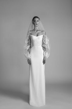 'RITA' WEDDING GOWN A fitted corset wedding dress with a twist featurnig oversized sheer lace and tulle sleeves a high side slit skirt and a