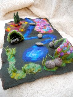 A Play mat comes with a cave river rocks stepping stones a forest area and a flower field Playscape Waldorf  Wet Felted by hand. $67.00, via Etsy.