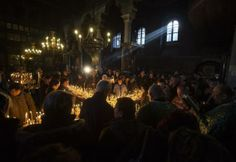Worshipers gather around candles stuck to jars with honey, during a religious mass in the church of the Presentation of the Blessed Virgin in the city of Blagoevgrad, some 100 km (62 miles) south of the Bulgarian capital of Sofia, February 10, 2014. The day of Saint Haralampi, the Orthodox patron saint of beekeepers, is marked on February 10.  REUTERS/Stoyan Nenov