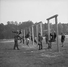 Liberators of Belsen Concentration Camp play with child survivors on a swing set. Soon after April 15th, 1945.
