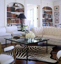 Love the zebra rug at angle And love white walls with book shelves but not in arched recess.