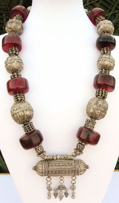 "by Sandra Destash | Necklace made from using pieces out of an antique Yemeni necklace, four cylinder shaped 'cherry' coloured African amber beads (early to mid 1900s).  All the large round silver beads bear a makers stamp, which says in Arabic - ""Sleman Almagrashi"", from one of the well-known Yemeni silversmith families. 