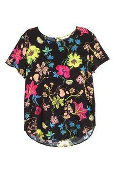 Bluzka z krótkim rękawem: Bluzka z krepowanej tkaniny wiskozowej. Krótki rękaw, na karku rozcięcie z guzikiem. Zaokrąglony dół i nieco dłuższy tył.