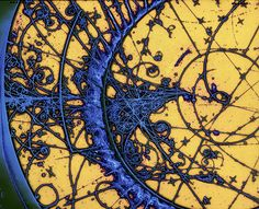 This is an image from a bubble chamber. It shows the paths made by tiny particles as they move through liquified gas. These spiraling tracks are caused by collisions between subatomic particles. The protons, neutrons and electrons that make the tracks are impossible to see directly.