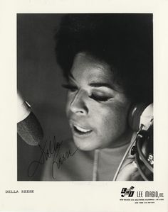 """Portrait of Della Reese, wearing headphones and singing into microphone. Printed on front: """"Della Reese. LMI, Lee Magid, Inc. 5750 Melrose Ave., Hollywood, California. HO 3-2353. New York (212) 947-7674."""" Autographed on front: """"Della Reese.""""  Courtesy of the E. Azalia Hackley Collection of African Americans in the Performing Arts, Detroit Public Library"""