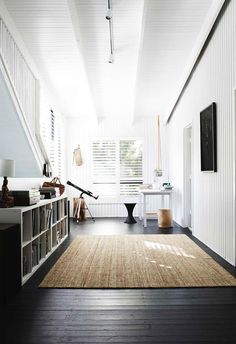 On the second floor, dark timber flooring is paired with stark white walls and a woven rug. A creative couple tackled the renovation of their chalet style cabin house in Noosa with no expert help but plenty of determination. Laminate Flooring Prices, Cheap Wood Flooring, Flooring Store, Best Flooring, Tile Flooring, Wood Laminate, White Wall Bedroom, White Walls, Bedroom Decor