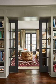 French doors invite daylight to flow through the den and the living room of this farmhouse. Pocket doors between the rooms slide closed for sound control.