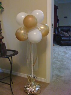 50th anniverary balloon bouquet. The dowel rod is inserted in a floral foam block with bags of beans to weigh it down, all covered in tissue paper!