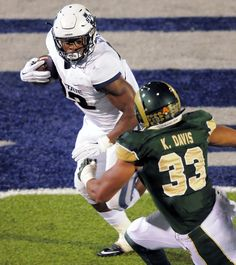 Utah State University running back Devante Mays (32) carries the ball as Colorado State linebacker Kevin Davis (33) defends during a game in Logan, Utah. Click through to see a photo gallery of the football game. (Photo by Eli Lucero)