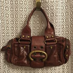 Francesco Biasia boho hand bag Large buckle closer with two zipper openings. Pockets with zippers on each side .. Ruffle detail on back with snap closure. Brown sticking detail lines around front. Great hand bag or any occasion! Used once only! Francesco Biasia Bags Mini Bags