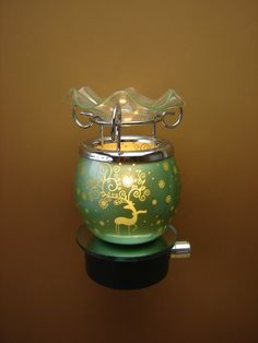 This adorable Green Reindeer Oil Burner is perfect for the holidays to welcome friends and family.   Tart warmer plugs directly into any wall outlet for happy holidays.  Add candle wax scent, burner oil, or potpourri and adjust the heat by the dimmer switch.  The dimmer switch has three settings, l