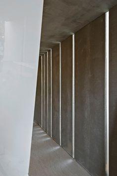 """Banheiros Públicos Ecotransportávies (containers navais) - arquitetos Sergio Vianna e Jonathas Valle - foram projetados para ser uma estrutura móvel. O interior tem revestimento em placas de Viroc que dispensam acabamentos como tintas e cerâmicas e dão um tom de cimento queimado às paredes. Para auxiliar na iluminação, a estrutura possui rasgos, que possibilitam a entrada de luz natural, e """"lâmpadas"""" de garrafas pet que também aproveitam a incidência solar. Casa Cor Minas Gerais 2013."""