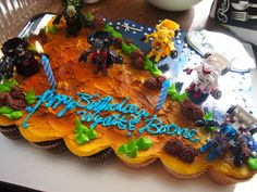 Daddy Complex: This was the boys' birthday cake, which is actually a collection of cupcakes. Since the guys are on a big robot/Transformers kick right now, my wife cleverly ordered a Toy Story-themed cake (desert side for Woody, space side for Buzz) and provided the Transformer toys for the decorations.  My mother-in-law sent two of the toys a while ago, which gave us the idea. My job was to get more of them. I also took on the duty of eating three of the cupcakes after the party.