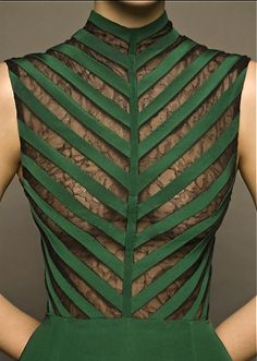This is a nip slip just waiting to happen, but structurally, I really dig it. It's like an exterior rib cage. ~ETS (Dina Jsr details...cut out sleeveless green dress with mesh lace backing)
