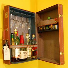 An old box or suitcase can make a sweet wall-mounted cocktail bar.