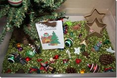 Symbols of Christmas sensory tub: split peas, small tree, Christmas bulb buttons, star box, poinsettia buttons, cinnamon scented pinecones, small plastic christmas ball ornaments, star buttons, gold star tree topper, small nativity set, wooden ornaments, small wreaths, symbols of Christmas printable book