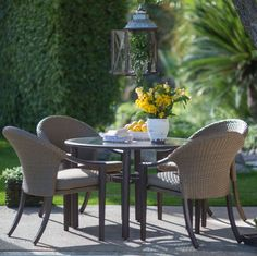 Inviting outdoor wicker patio dining chair and glass top table set 4 fabric cushions covers dark brown metal frame with mottled black antiquing umbrella hole.
