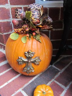 c988cb957 Embellishment a pumpkin by attaching something to the front - here, a  cross. Also add a floral spray/ribbon to dress it up.