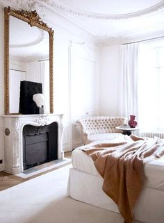 The French Bedroom Company Blog Gives their tips on How to Style Your Bedroom Like a Parisienne. Including white walls, eclectic style, boho chic, mid century chair and french upholstered bed. This Paris apartment is the epitome of french chic with high ceilings, grand fireplace, white walls, large windows and pink sofa. Parisian Perfection