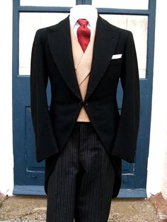 DB buff waistcoat with grey striped trousers, black tails and red 4 in hand tie.