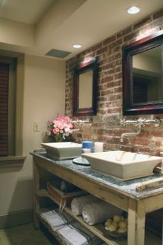 Bathroom With Brick And Wall Mount Faucets, Vessel Sinks.