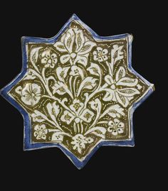 AN ILKHANID LUSTRE STAR TILE, PERSIA, EARLY 14TH CENTURY of eight-pointed stellar form, the fritware decorated with a lustre depiction of a foliate palmette with a cobalt blue border