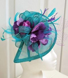The most impressive rich bright teal color fascinator with multiple swirls is decorated with 2 shades lavender flowers, matching feathers and
