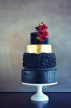 Deep and dark, rich black wedding cake with stripes, ruffles and gold leaf. Adorned with vibrant red sugar roses and berries. www.countrycakeshop.com