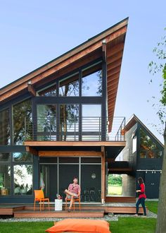 This lakefront home designed by Kristen L'Esperance features a soaring roof, horizontal wood paneling, and floor-to-ceiling windows that take advantage of the gorgeous natural scenery.