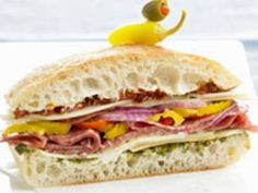 Tote-and-slice Loaf Sandwich--¾ cupDried Tomatoes (not Oil-packed) 1× 1-lbLoaf Italian or French Bread ½An 8-oz. Pkg. Cream Cheese, softened ⅓ cupBasil Pesto 4 ozThinly Sliced Provolone Cheese 8 ozThinly Sliced Peppered or Regular Salami 1Medium Fresh Banana Pepper or 8 Bottled Peppers, stemmed, seeded, and sliced 4 ozThinly Sliced Provolone Cheese ½Medium Red Onion, thinly sliced Small Salad Peppers &/or Pimiento-stuffed Green Olives (optional)