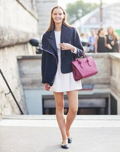 A patterned coat is worn over a white mini dress, black flats and a red Céline Tie bag