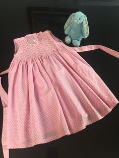 Pretty pink and white dotted dress with smocking and hand embroidered flowers.