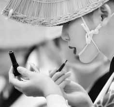Awa odori dancer is adding her lipstick before the show.