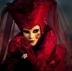 A stunning image by Nora de Angelli. The blood reds, the shadows, and the red eyes evoke The Beast in Human Form.  The mystery and sensuality of Carnivale. Masked images from Carnivale don't get much better than this.  http://500px.com/photo/5205401
