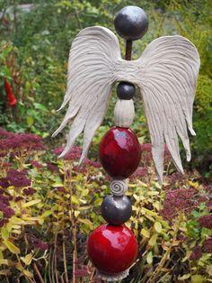 Wunderschöne Gartenstele mit Engelsflügeln. Die Stele besteht aus 9 Elementen, die alle frostfest gebrannt sind. Kugel und Olive sind mit einer Glasur in unterschiedlich dunkel verlaufenden...
