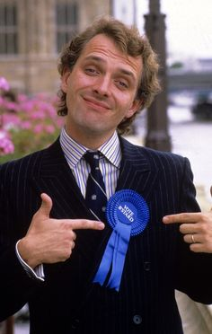 Mayall played fictional Conservative MP Alan Beresford B'Stard in the sitcom The New Statesman, written by Laurence Marks and Maurice Gran, which aired in 1987. | 9 Hilarious Moments To Remember Rik Mayall By
