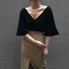 "Perfect double side v-neck blouse in black with triangle sleeves, just long enough to tuck into a high waist pencil skirt with a front slit.  I'd love to see this with run-of-the-mill black pumps or taupe open-toe suede ankle boots with a shorter chunky wooden heel or open side & back ankle boots in taupe with an ankle buckle and covered/flat front.  Add a silver ""Y"" shape necklace."