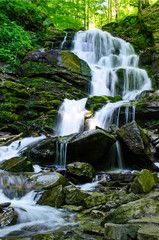 Landscape with a beautiful waterfall and a mountain river in the