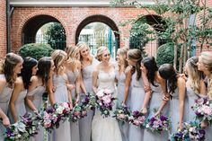 bride and her bridesmaids in pale grey gowns carry their bouquets of light pink peony, ocean song rose, dark purple stock, dried lavender,  light pink ranunculus, lavender lisianthus, dusty miller, burgundy scabiosa, pink wax flower, white majolik spray rose, bay leaf, fern, silver dollar eucalyptus & vines wrapped in cream satin ribbon.
