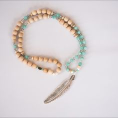 Boho Necklace with Feather Pendant Make a statement with this a gorgeous light wood and turquoise color beaded necklace with a silver feather pendant.    This piece is one of a kind and made by Boho Beads by Stella located outside of Philadelphia. Boho Beads by Stella Jewelry Necklaces