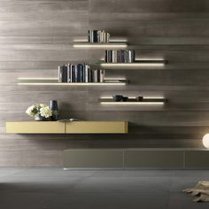 An innovative wall shelving system: the Eos design combines, in only 8 mm, a lacquered glass top with a lacquered aluminium frame, blending aesthetic variety and maximum reliability. The wall anchoring system, which ensures installation with no exposed screws, includes a LED lighting system.