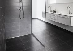Patented Linear Wall Mounted Drain with a solid stainless steel panel and integrated glass screen. One slope , large tiles , less grout lines and no need to stand on the drain in the shower.
