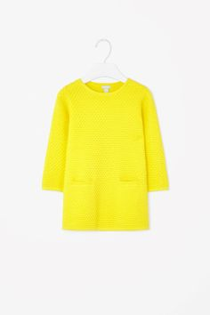 This dress is made from raised-knit cotton with a modern scalloped texture. A relaxed fit that flares slightly towards the hemline, it has fitted long sleeves, a neat round neckline and two flat pockets on the front.