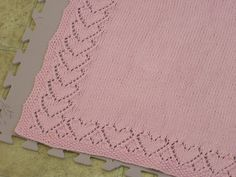 Baby blanket made with a lace heart motif and seed stitch border.