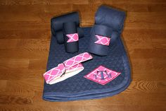 Equine Full Set - Navy with Fuchsia Quatrefoil Diamond Applique by KLMequestrian. Show off in this complete gift set for you and your horse! Customized with your monogram on the saddle pad. 1 Monogrammed saddle pad with circle applique . 4 Standing wraps (horse or pony size), 4 Polo wraps (horse or pony size), 1 D-ring adjustable belt (adult or youth)