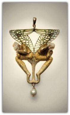 RENÉ LALIQUE | Broche en or et émail représentant 2 figures ailées à décor symboliste, tenant dans leur main leur tête en ivoire. Les corps en relief posés sur un motif floral, les ailes en émail plique à jour. Elle est agrémentée d'une perle en pampille. Porte la signature LALIQUE au dos à droite. Manque épingle, probablement transformée ultérieurement en pendentif. Légers manques à l'émail.