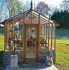 Garden Deluxe Greenhouse by Sturdi-Built. Stone base wall and architectural details like eave overhangs, arched door, and finial make this a real eye-catcher!