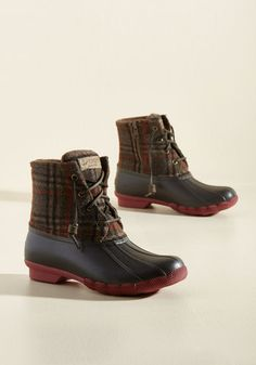 When the weather gets chilly, treat your toes to these brown duck boots from Sperry! This classic style touts leather laces, maroon-and-green-touched plaid uppers, and rubber bases and soles, assuring that your feet are warm, dry, and totally fly when Mother Nature casts coldness into the air.
