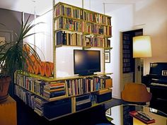 DIY shelving dividing wall creates a separate bedroom and gives lots of storage in this 420 square feet small studio apartment