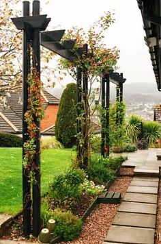 This long, narrow arbor adds vertical interest to the garden. Love the pathway.